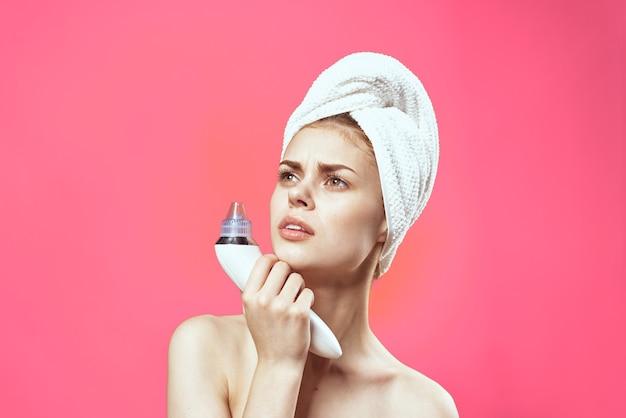 Mulher alegre com uma toalha na cabeça aspirador de pó limpando o fundo rosa