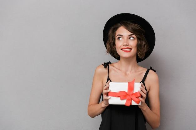 Mulher alegre com vestido preto e chapéu segurando uma caixa de presente, isolada sobre uma parede cinza