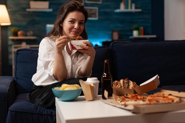 Mulher alegre comendo comida chinesa saborosa e relaxando no sofá