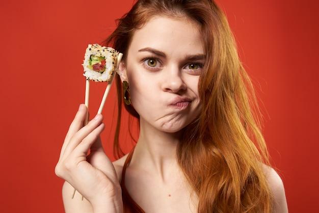 Mulher alegre comendo sushi comida asiática com fundo vermelho