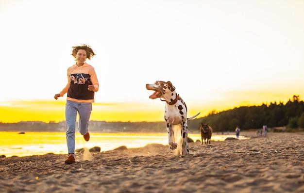 Mulher alegre correndo com cachorros na praia
