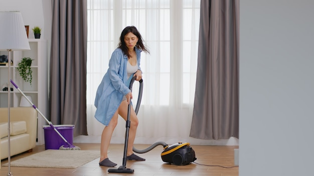 Mulher alegre dançando enquanto limpa o chão usando aspirador
