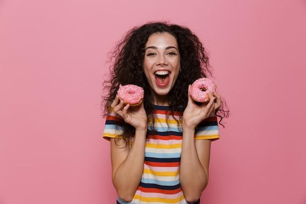 Mulher alegre de 20 anos com cabelo encaracolado se divertindo e segurando rosquinhas isoladas em rosa