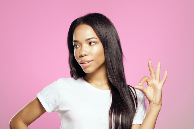 Mulher alegre de aparência africana em camiseta branca, cabelo comprido fundo rosa