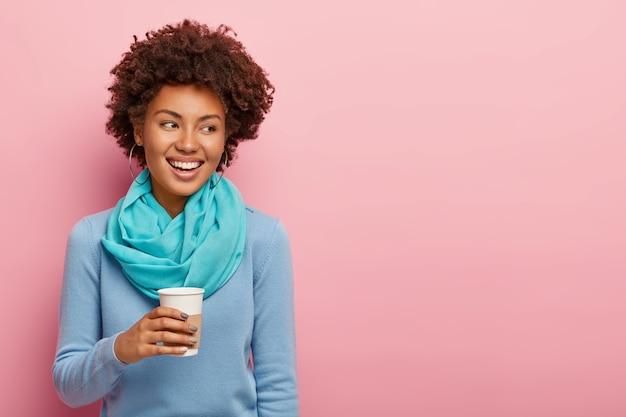 Mulher alegre de aparência agradável com cabelo afro bebe café para viagem, aproveita o descanso após um árduo dia de trabalho, conversa agradável olha de lado com sorriso dentuço vestida com roupas azuis isoladas na parede rosa
