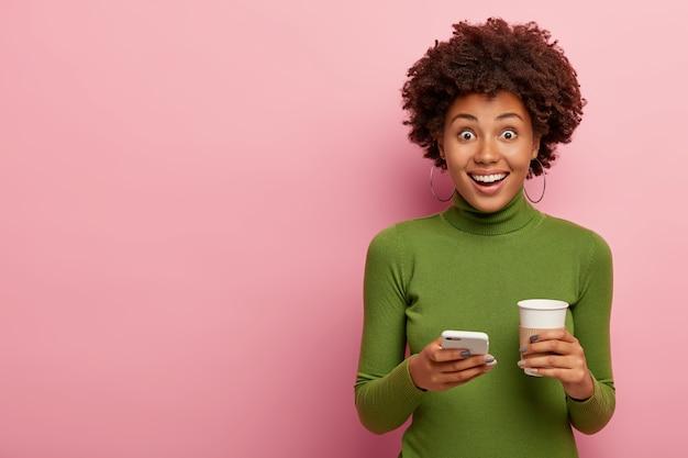 Mulher alegre de cabelos cacheados e pele saudável, usa uma rola verde casual, segura o celular moderno e café para viagem, gosta de comunicação online