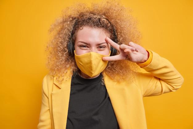 Mulher alegre de cabelos cacheados faz gesto de paz sobre os olhos e se diverte ouvindo música através de fones de ouvido e usa máscara protetora durante poses de pandemia contra parede amarela vívida conceito de linguagem corporal