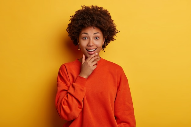 Mulher alegre de cabelos cacheados segura o queixo e expressa emoções brilhantes