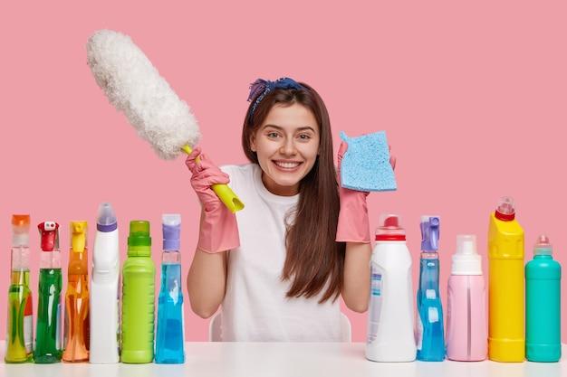 Mulher alegre de cabelos escuros carrega pano e escova, sorri feliz, vestida com roupas casuais, senta-se à mesa branca com produtos de limpeza