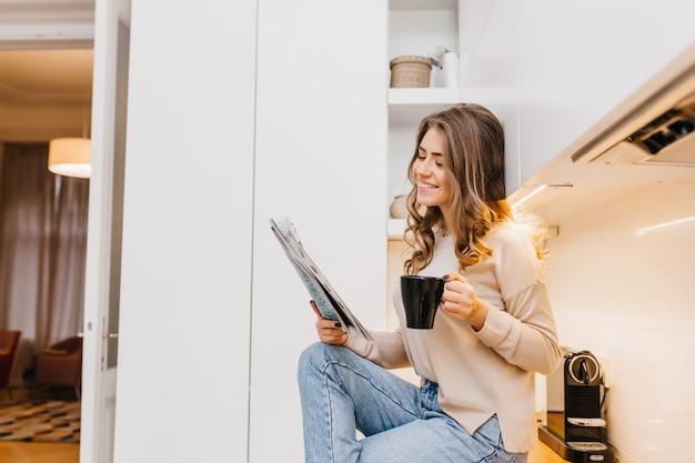 Mulher alegre de cabelos escuros passando a manhã em casa lendo jornal com sorriso