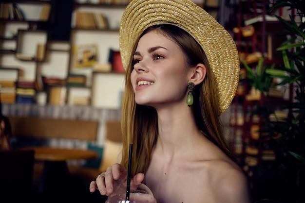 Mulher alegre de chapéu sentada em um café com livros de estilo de vida