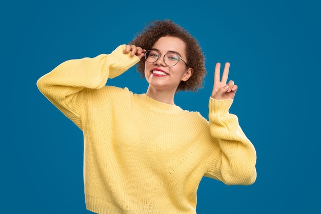 Mulher alegre de óculos mostrando o sinal v