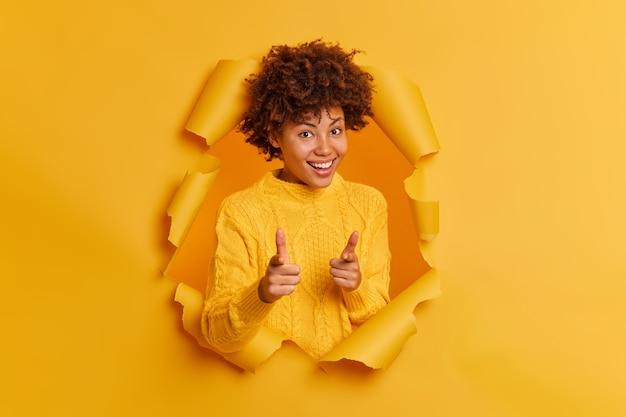 Mulher alegre de pele escura aponta o dedo indicador para a câmera e escolhe alguém