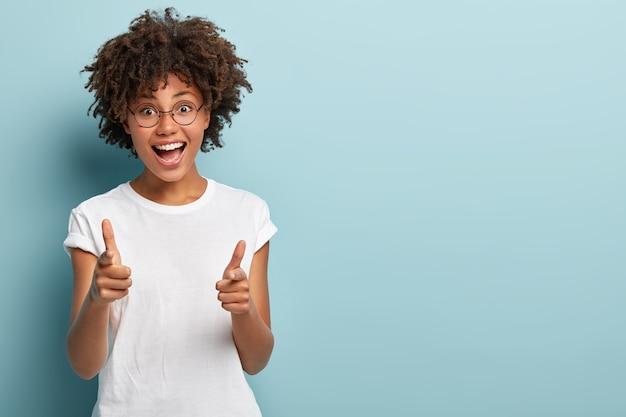 Mulher alegre de pele escura apontando os dois dedos da frente diretamente para a câmera
