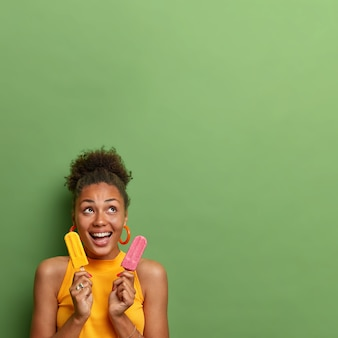 Mulher alegre de pele escura com cabelo penteado encaracolado ri alegremente, concentrada acima, se diverte durante o dia quente de verão, come um delicioso sorvete, isolado sobre a parede verde. sobremesa gostosa
