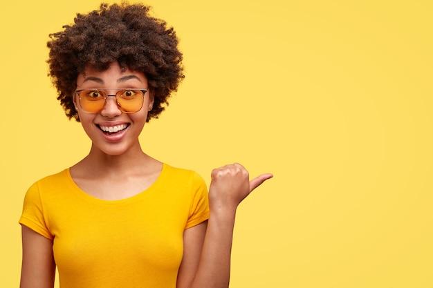 Mulher alegre de pele escura com corte de cabelo afro, aponta para o lado com o polegar, satisfeita com os preços de promoção, usa óculos escuros e camiseta casual