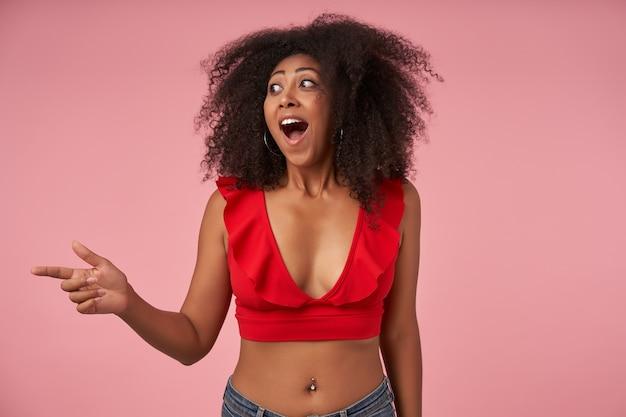 Mulher alegre de pele escura, com top vermelho e jeans olhando para o lado com a boca bem aberta e apontando com o dedo indicador levantado, em pé na rosa com rosto surpreso