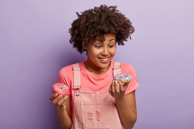 Mulher alegre de pele escura comendo um donut delicioso