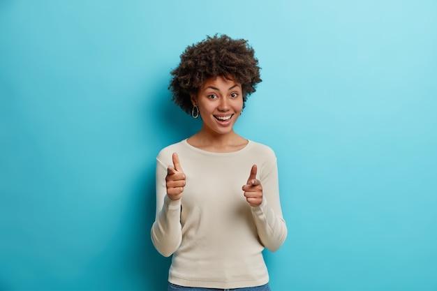 Mulher alegre de pele escura e cabelo encaracolado seleciona alguém fazendo gesto de arma com o dedo
