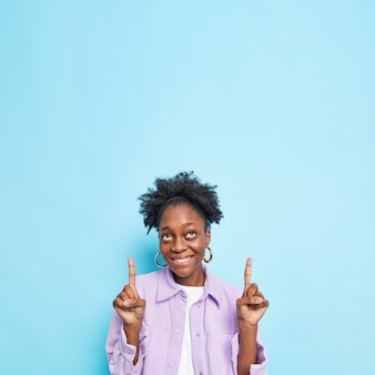 Mulher alegre de pele escura e cacheada indica acima mostra incrível oferta aponta o dedo indicador para cima demonstra texto promocional para cima