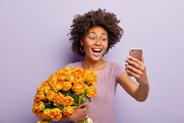 Mulher alegre de pele escura expressa sentimentos e emoções sinceros, faz selfie para compartilhar fotos em rede social, segura um belo buquê grande de flores de laranja, usa camiseta casual,