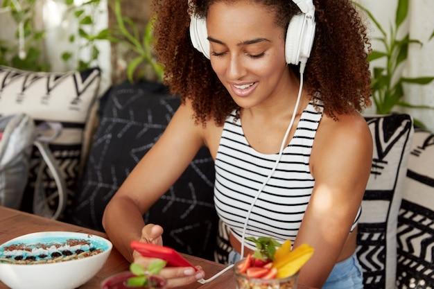 Mulher alegre de pele escura verifica a caixa de e-mail on-line no smartphone, conectada à internet sem fio em uma cafeteria, ouve música popular bacana em fones de ouvido, faz download de um audiolivro, come sobremesa