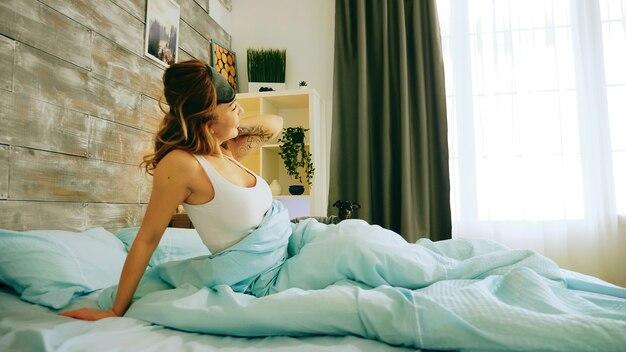 Mulher alegre de pijama, acordando de manhã cedo. pequeno cachorro.