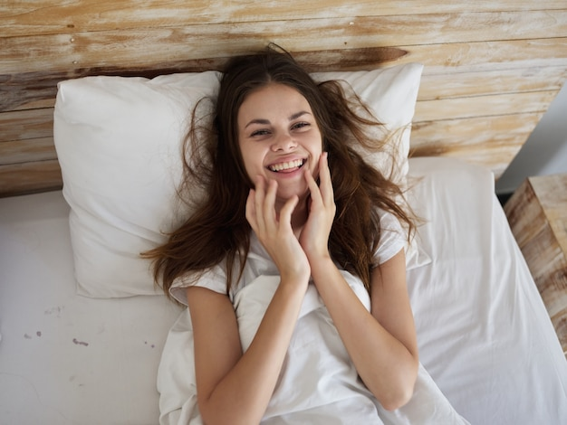 Mulher alegre deitada na cama sorri alegria matinal