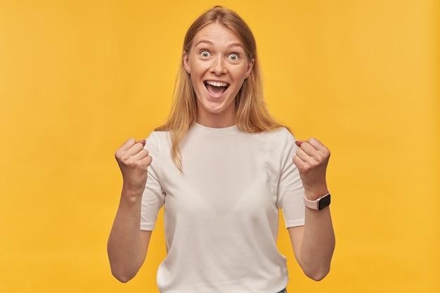 Mulher alegre e animada com sardas na camiseta branca mantém as mãos levantadas, gritando e comemorando a vitória no amarelo