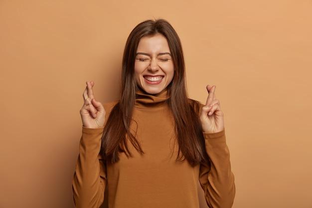 Mulher alegre e animada sorri amplamente, cruza os dedos, espera que os sonhos se tornem realidade, usa gola olímpica marrom, acredita na boa sorte