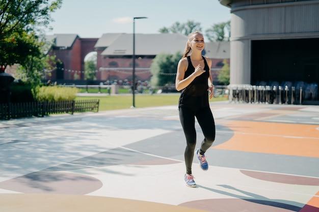 Mulher alegre e atlética corre ativamente no estádio vestida com roupas esportivas pretas e gosta de atividades físicas ao ar livre durante o dia de verão, estando cheia de energia. conceito de esporte e motivação de pessoas
