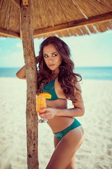 Mulher alegre e atraente de biquíni segurando um coquetel na praia em um dia ensolarado