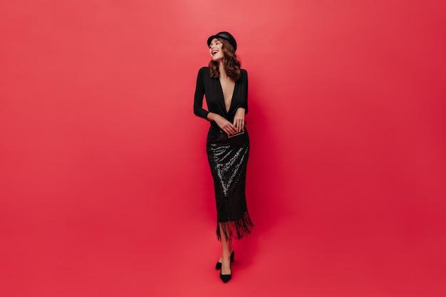 Mulher alegre e cacheada em um vestido preto brilhante midi rindo, segurando a bolsa de mão e fazendo poses na parede vermelha