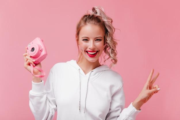 Mulher alegre e cacheada posando com a frente rosa