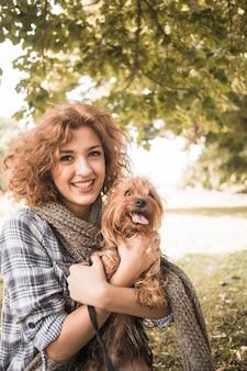 Mulher alegre e cachorro engraçado no parque