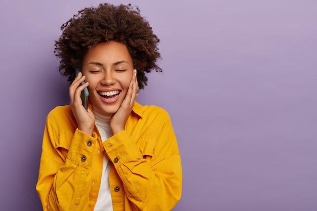 Mulher alegre e despreocupada com penteado encaracolado conversa engraçada com o melhor amigo via smartphone, mantém os olhos fechados e sorri amplamente