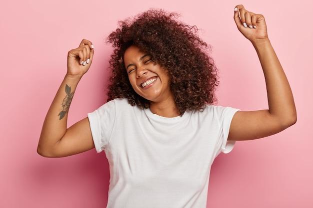Mulher alegre e divertida levanta os braços e dança despreocupada, sente prazer e se diverte, ri feliz, olhos fechados de satisfação, acompanha a música, tem tatuagem vestida com roupa casual isolada no rosa
