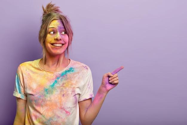 Mulher alegre e encantada brinca com as cores do holi, se diverte no festival, aponta com o dedo indicador, anuncia o espaço da cópia, gosta de cores vivas salpicadas no rosto e na camiseta, faz gestos sobre a parede roxa