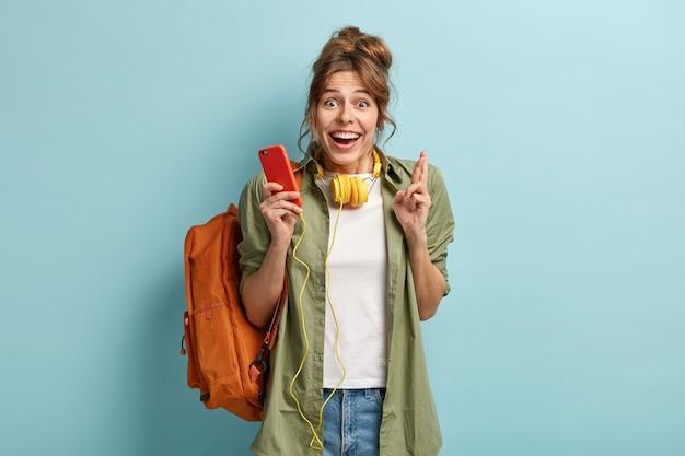 Mulher alegre e encantada usa fones de ouvido, ouve música de um aplicativo em um celular moderno e cruza os dedos para dar sorte