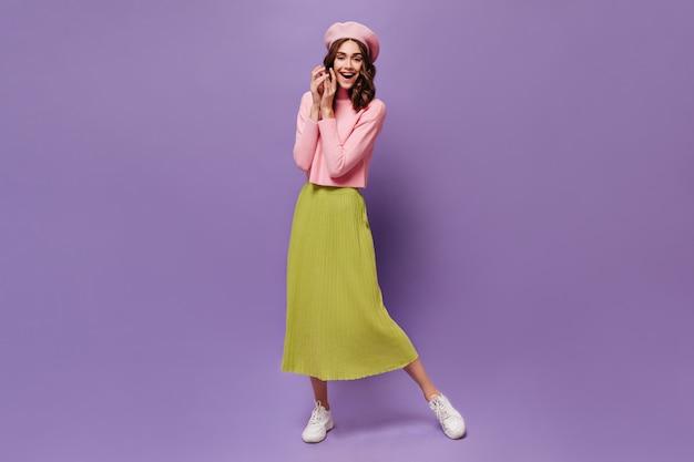 Mulher alegre e encaracolada com saia midi e boina sorrindo na parede roxa