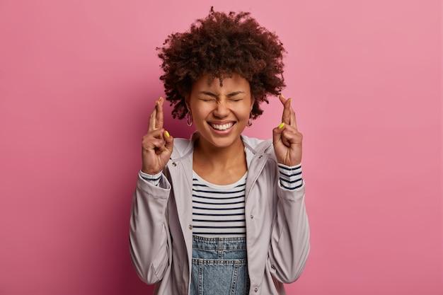 Mulher alegre e étnica cruza os dedos, deseja fortuna e vitória