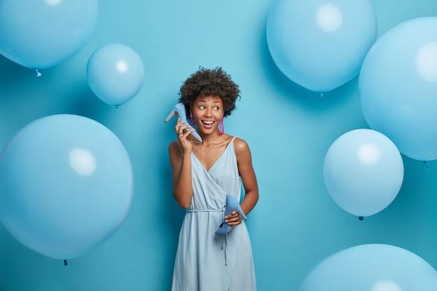 Mulher alegre e étnica escolhe sapatos de salto alto para caber no vestido, se prepara para um evento especial, gosta da cor azul, imita telefonema com calçados, vestida com uma roupa da moda, posa em torno de balões