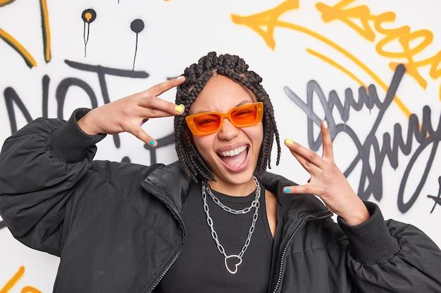 Mulher alegre e étnica legal com dreadlocks que faz o gesto de yo se divertir vestida com uma jaqueta preta e óculos de sol laranja elegantes sorrisos largamente posados contra parede de grafite