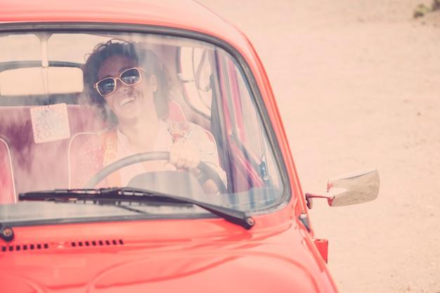 Mulher alegre e feliz, caucasiana, mulher de meia-idade, sorriso e risada, dirigindo seu belo carro retrô antigo