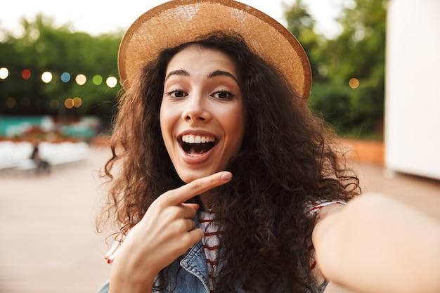 Mulher alegre e feliz com cabelo castanho cacheado, sorrindo e apontando o dedo para o lado enquanto tira uma foto de selfie ao ar livre