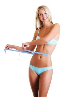 Mulher alegre e feliz com um corpo esguio de beleza mede a cintura com fita métrica. sobre o espaço em branco.