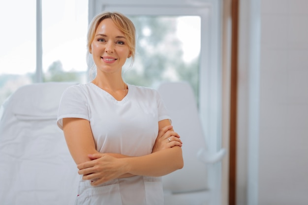 Mulher alegre e feliz em pé com as mãos cruzadas enquanto trabalhava como cosmetologista
