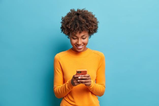 Mulher alegre e feliz olha para a tela do telefone inteligente gosta de bate-papo on-line, tipos de mensagem de texto, surfa nas redes sociais vestida casualmente, posa contra a parede azul