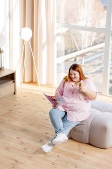 Mulher alegre e feliz sorrindo enquanto lê uma revista sobre beleza