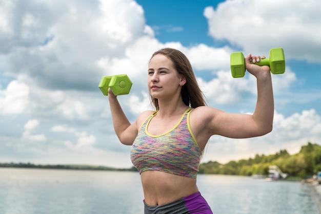 Mulher alegre e fitness em roupas esportivas, se exercitando com halteres, ao ar livre